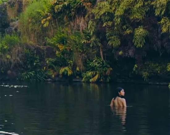ハワイの大自然で泳ぐ水着の女性